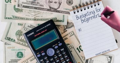 money bills laying on table with calculator and lady writing budgeting for beginners on pad